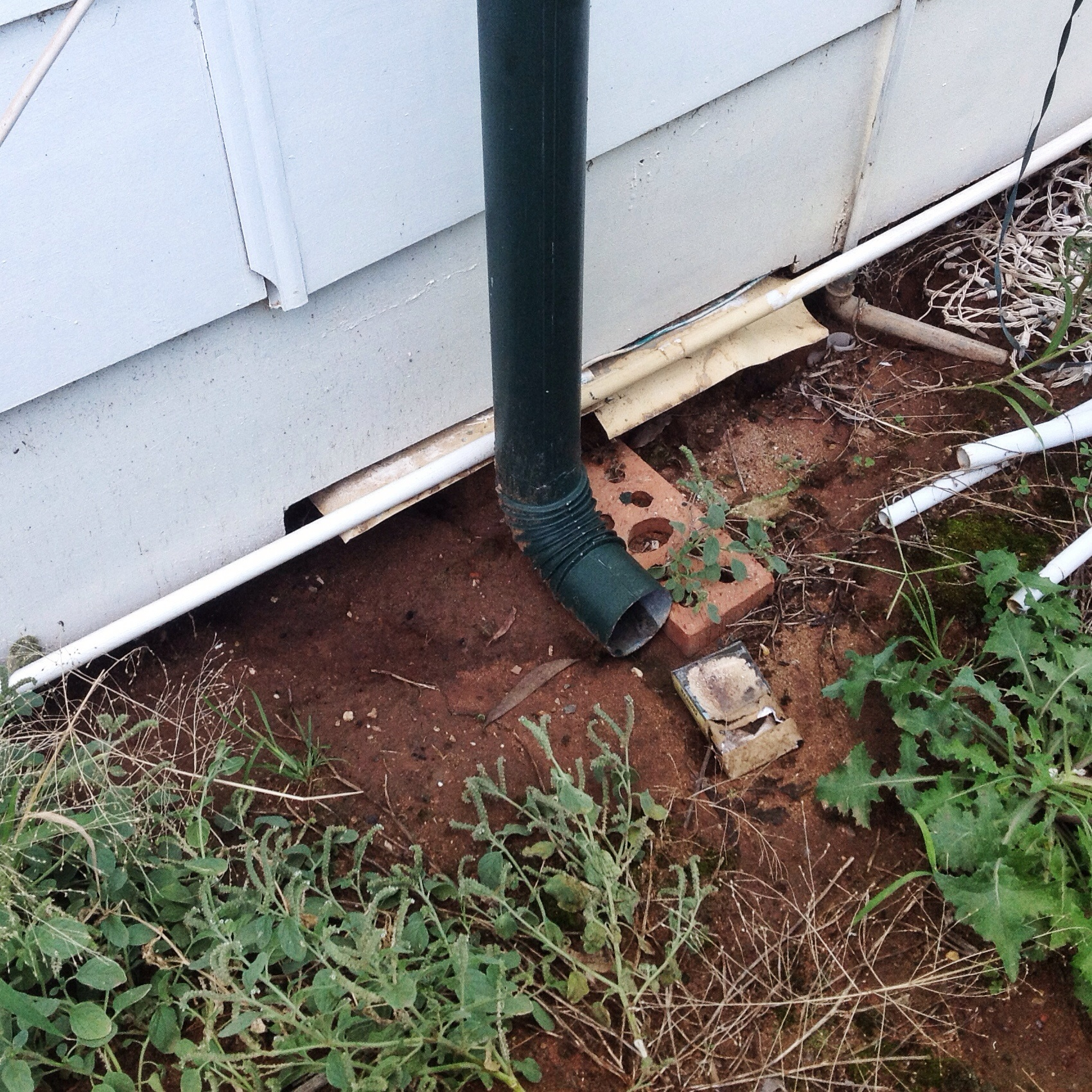 A downpipe draining against a building, it's like a pub with free beer for termites!