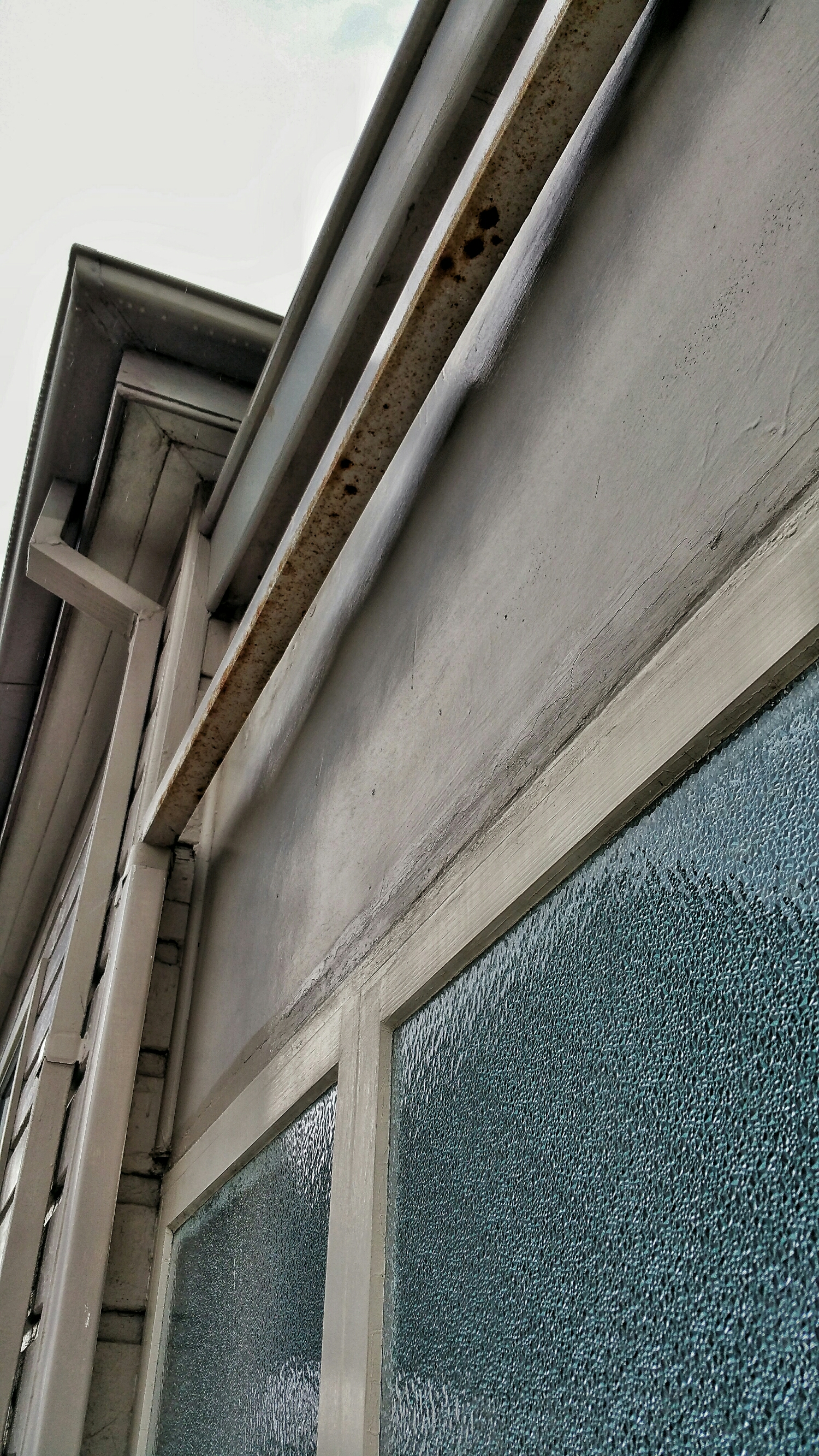 The downpipe above this window provided all the moisture required for the window below to rot.
