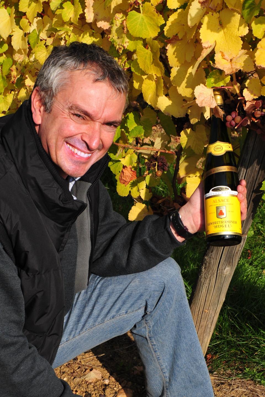 Etienne Hugel in the vineyard at the end of harvest with a bottle of gewurztraminer (Photo: Hugel)