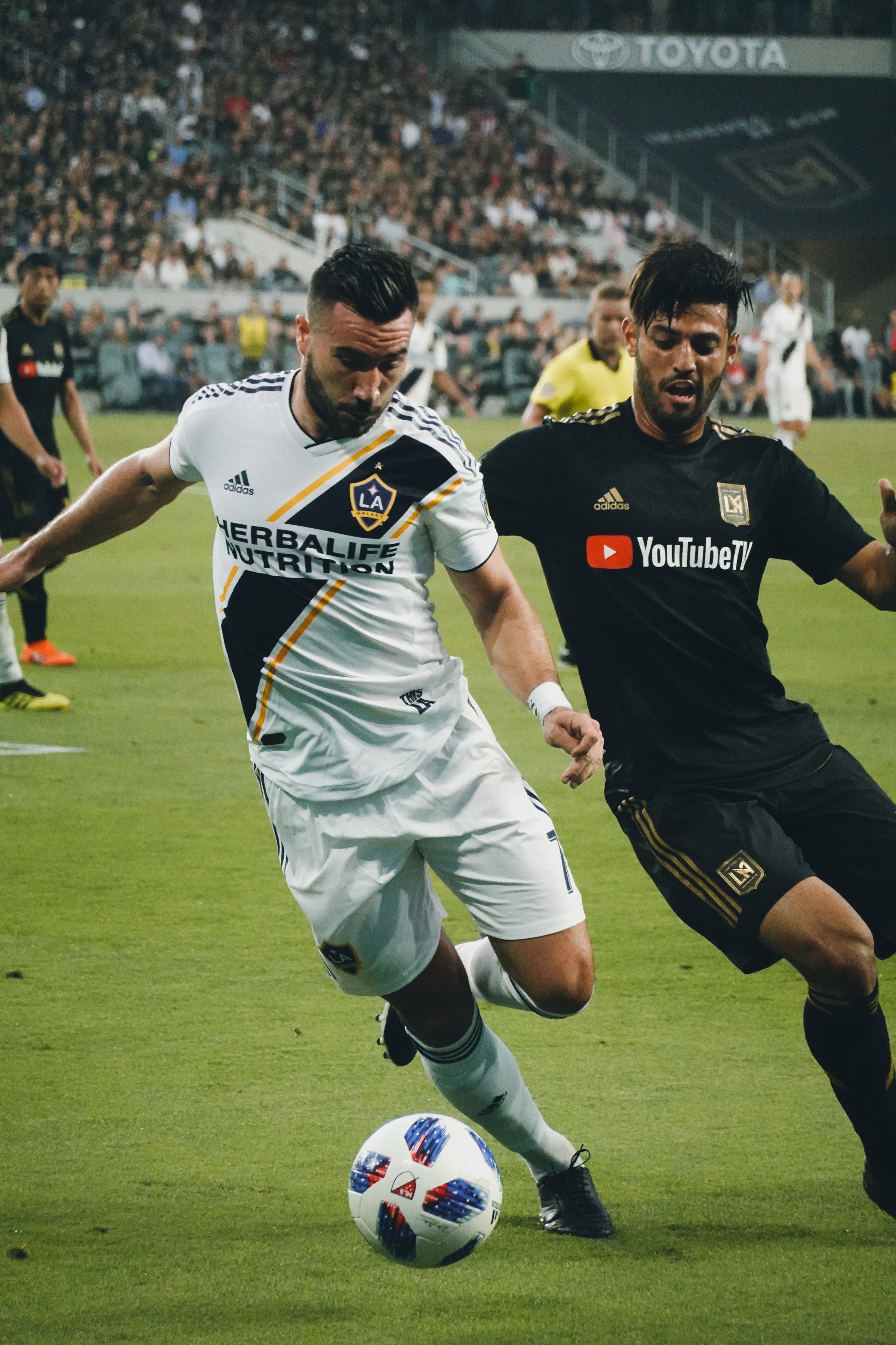 Carlos Vela battles Romaine Alessandrini, of the LA Galaxy for the ball in the LA Derby