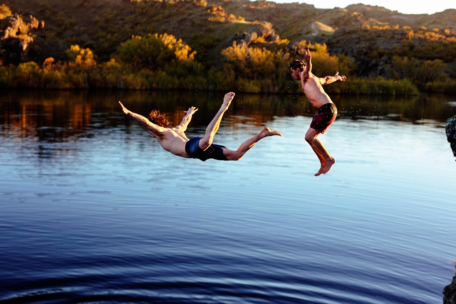 Two young men Jumping Into a lake