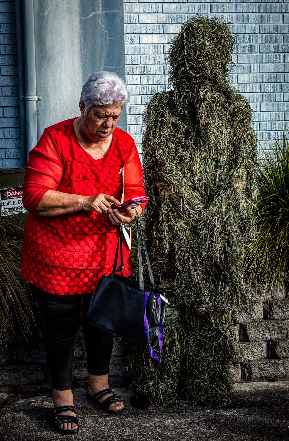 Old woman stands next to camouflage man on the street in onehunga-auckland-new zealand-spid pye_963__B6C0879.jpg