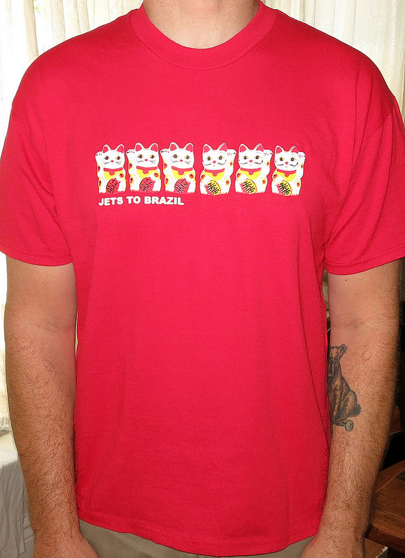 "theminorthread :      Day : 1094    Shirt : Jets To Brazil - Fortune Cats    Color :  Red    Brand : Hanes Heavweight 50/50    Source :  I really find the whole Jets To Brazil thing really interesting.  its kind of a band project that came out of the blue and didn't have much like it out in the music scape at the time.  while at the time it seemed to be hit or miss for  a lot of people, but i think the albums aged really well.    listening them today, 15 years later they almost seem more relevant sounding now than they did back then.  i know people would give their left nut for a Jawbreaker reunion but i would be a guy who would fly someplace to see these guy play again for real. not like a one off show, but a real ""lets do this band again"" situation."