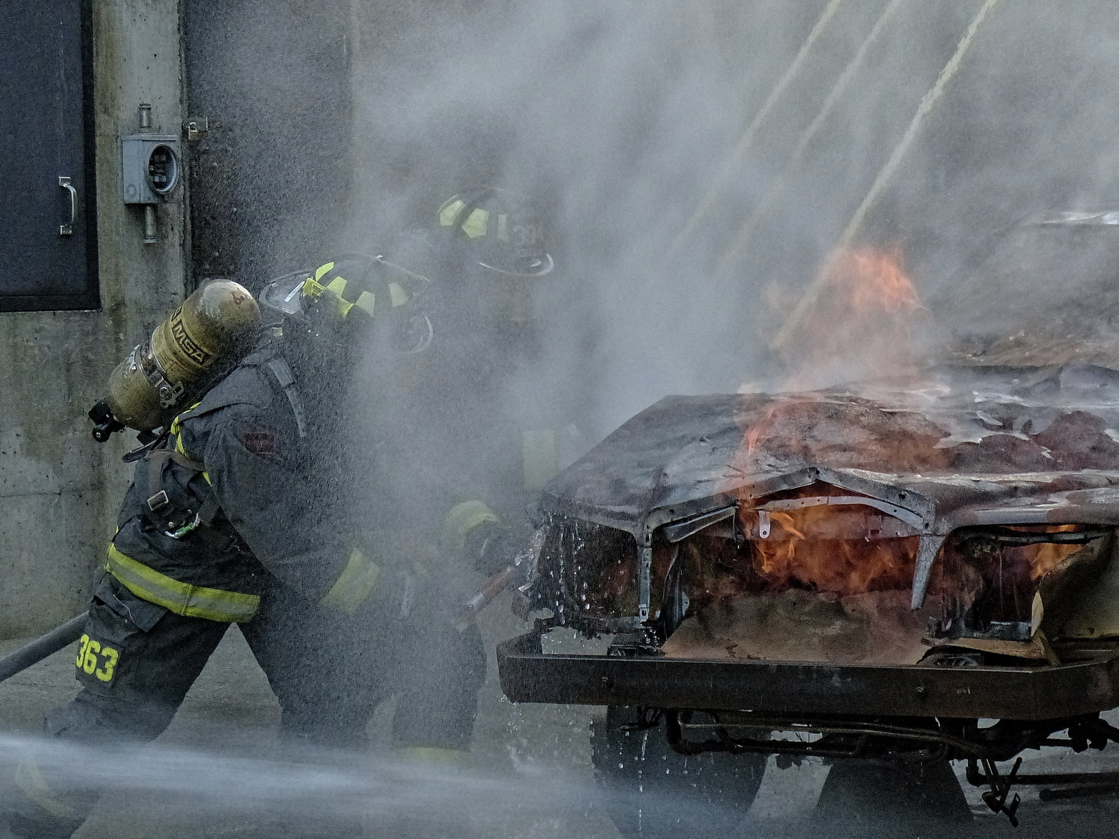 Prying open the hood of a car on fire