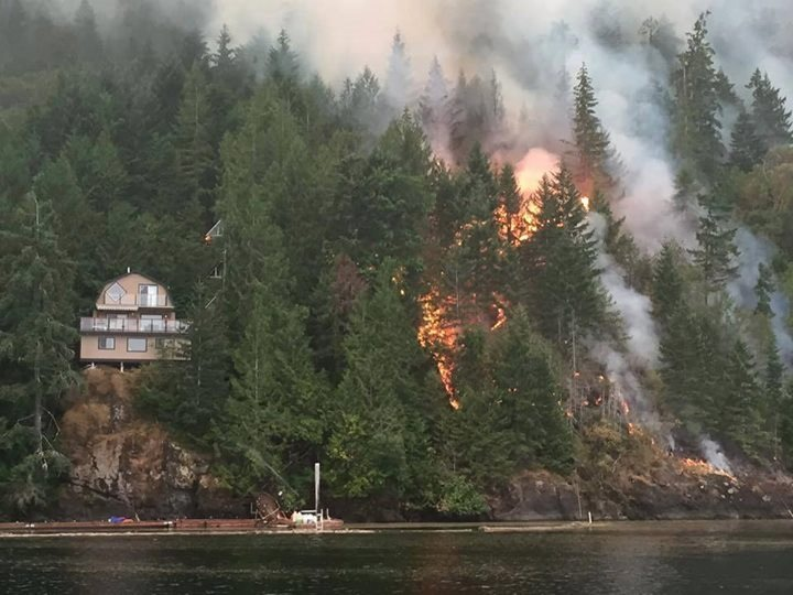 This photo shows the proximity of the fire to one of the homes the Comox Fire Department crew was called on to protect.    —Image Credit: Photo Submitted