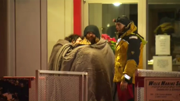 A trio of boaters huddle for warmth after being rescued from the frigid waters off Comox, Wed., Jan. 20, 2016. (CTV Vancouver Island)