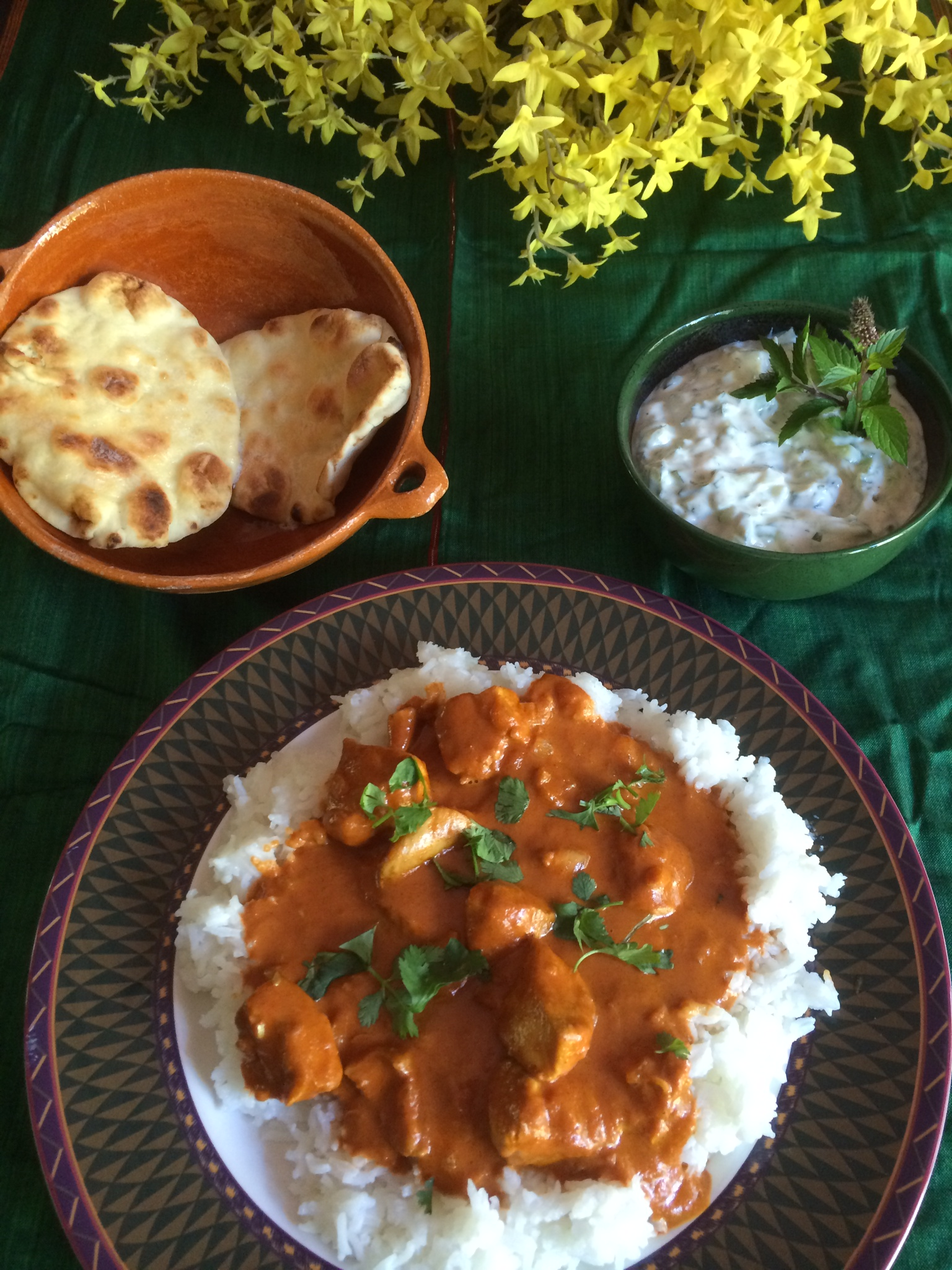 Perfectly spiced chicken tikka masala, served with basmati rice, naan, and  cucumber-mint raita .