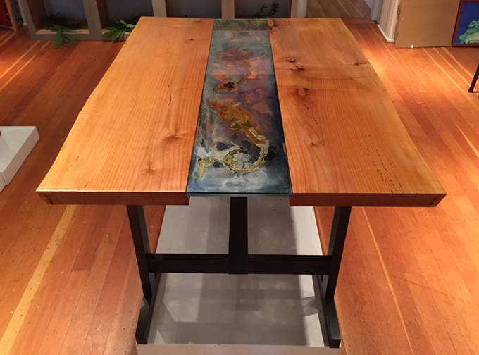 """The River table is locally milled Salt Spring Alder with a ebonized alter trestle leg system. The entire table will flat pack for shipping purposes. The artwork is is an original Plexiglas work inspired by the river, and contains embedded local botanicals. The table is 53"""" long by 37 3/4"""" wide, and 30.5"""" in height. On island shipping included. $3250."""