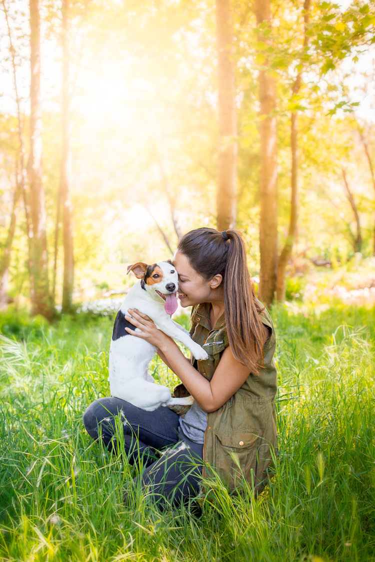 Girl smiling while holding her Jack Russell Terrier.