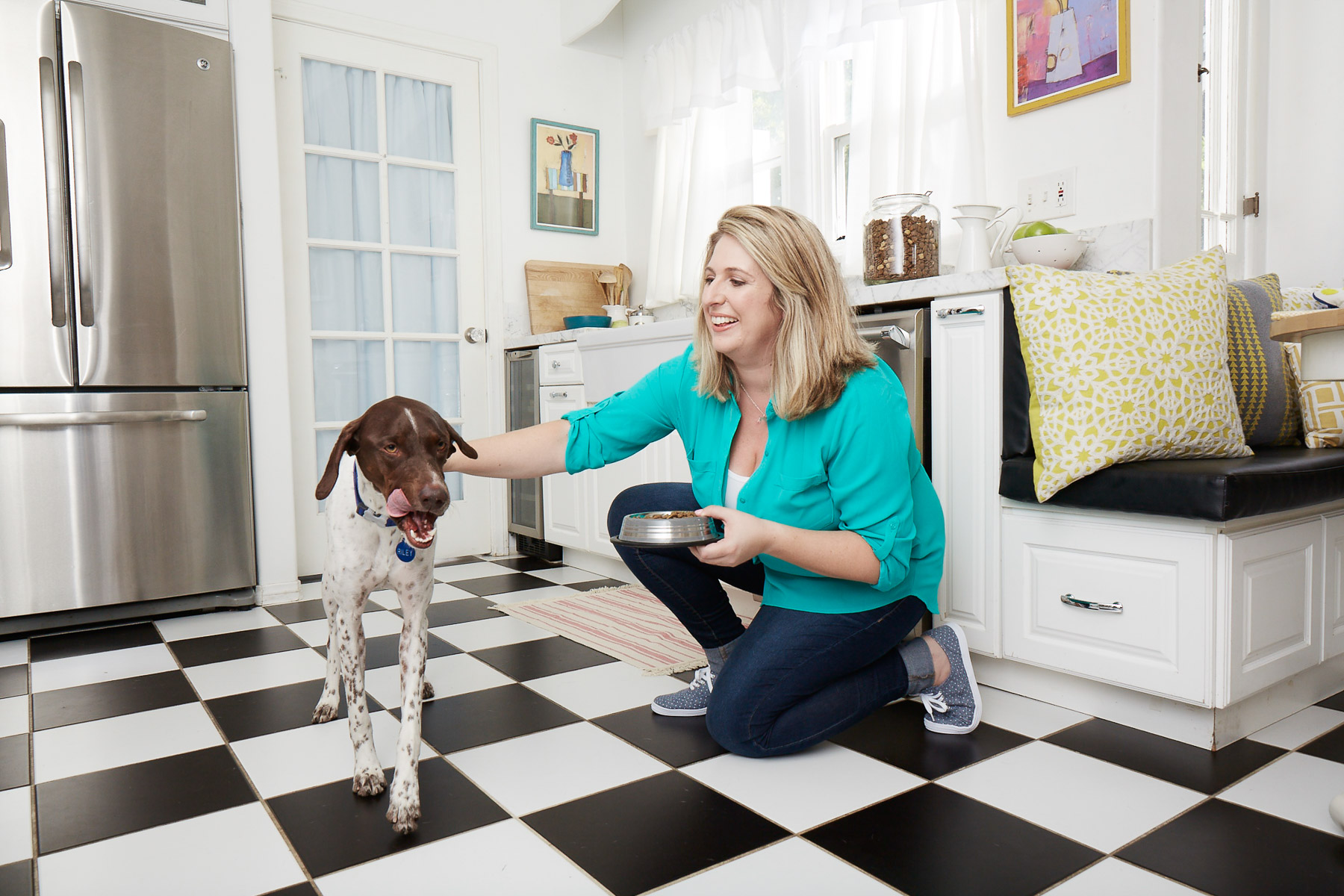 commercial-animal-photographer-blond-woman-feeding-dog-kitchen.jpg