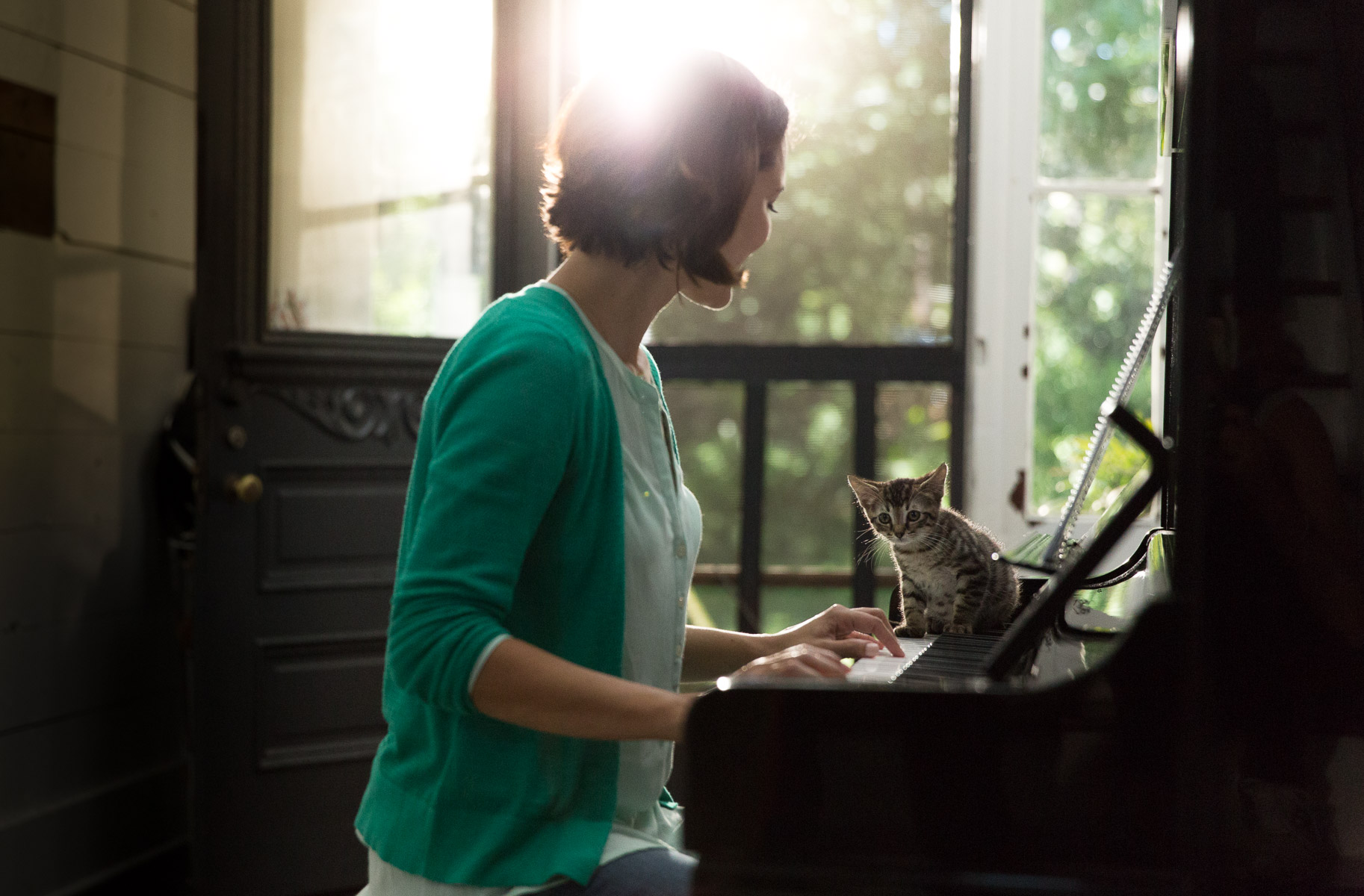 woman-playing-piano-with-cat-on-keyboards-pet-photography.jpg