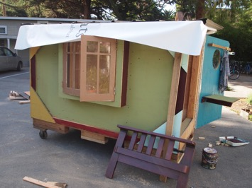 Pictured: House #1, wooden crate on wheels turned into a colorful home complete with pot-lid windows, roofing, a door, and trimming.