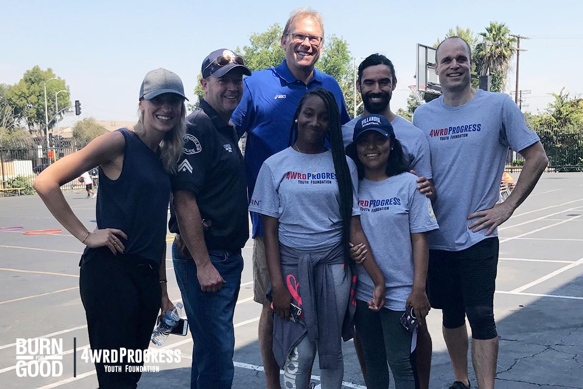 Operation progress kids Petra and Kim, Jenia, Ricardo, Andrew and Officer Jonny share a celebrity moment with Kurt Rambis.