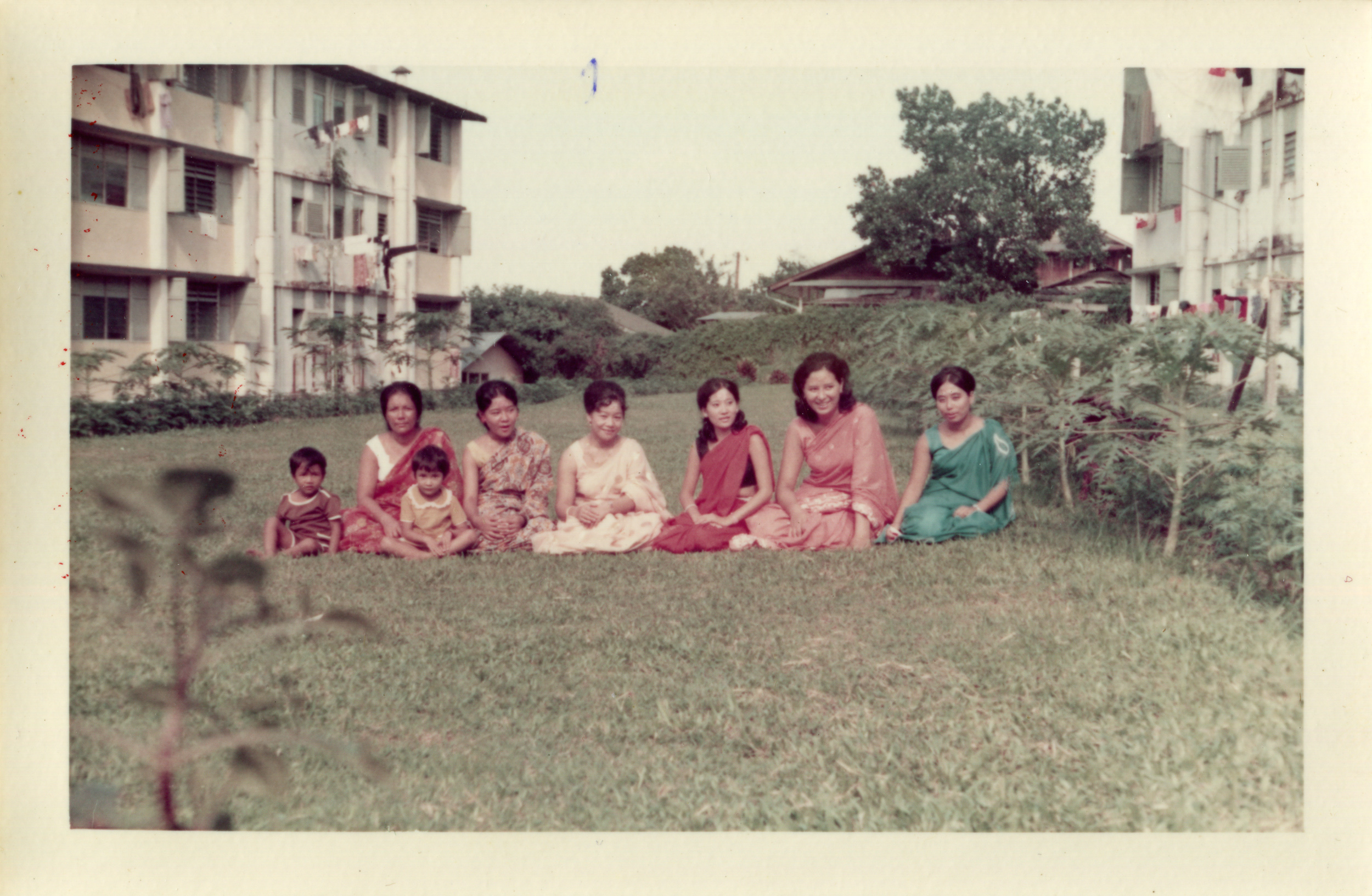 Singapore Gurkha wives and children sitting on the grass sandwiched between Block L (left) and Block M in Mount Vernon Camp. Date: 1971. Photo Collection: Aswin Tamang /SGPM.
