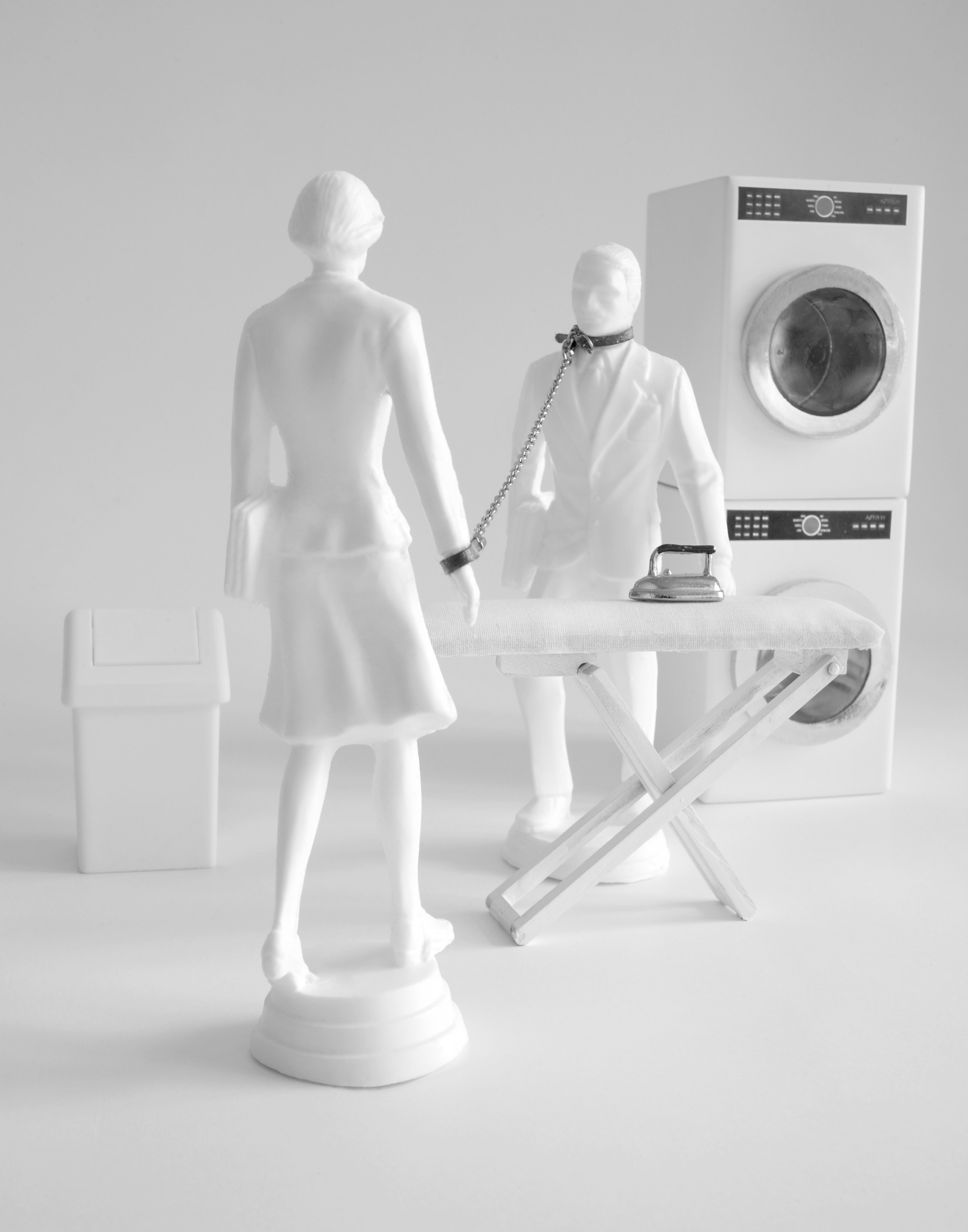 Dirty Laundry Secrets , 2010  Photograph in archival ink on rag paper  26 x 32 inches   Dirty Laundry Secrets  centers two anonymous white figures, a man and a woman, poised for a standoff in their laundry room environment. A chain runs from a cuff around the woman's wrist to a similar cuff wrapped around the man's neck. An ironing board separates them, becoming a barrier from what seems to be a harshly antagonistic scene. The viewer is left to decide who in the scene is making the demands.