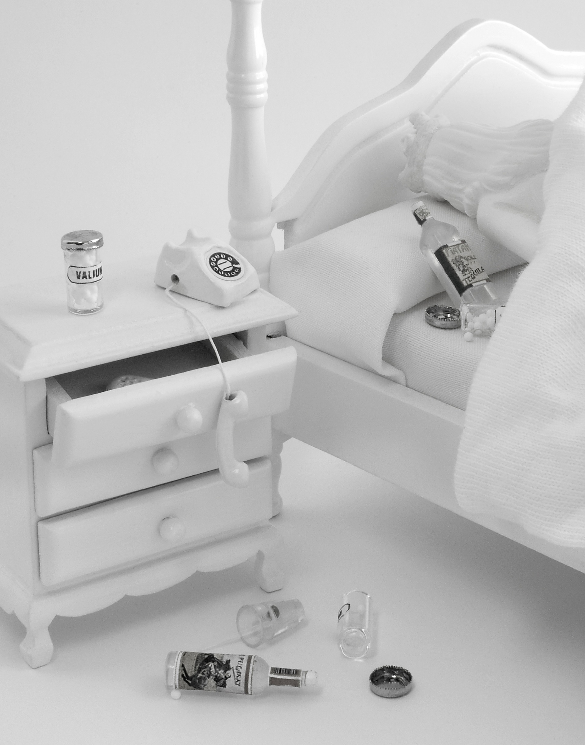 Get HIM to Forgive You , 2010  Photograph in archival ink on rag paper  26 x 32 inches  This work depicts a detail of a bed and side table, empty liquor bottles and pills littering the scene. The phone is left off the hook, dangling over an ajar drawer in which a bottle of Valium can be seen. A liquor bottle and ashtray rest on the pillow. In the corner of the picture plane, the beauty queen's head is just visible - she lies face down on her pillow. The viewer is left to wonder about the severity of the situation: is she sleeping off the hangover, or is it more dire?