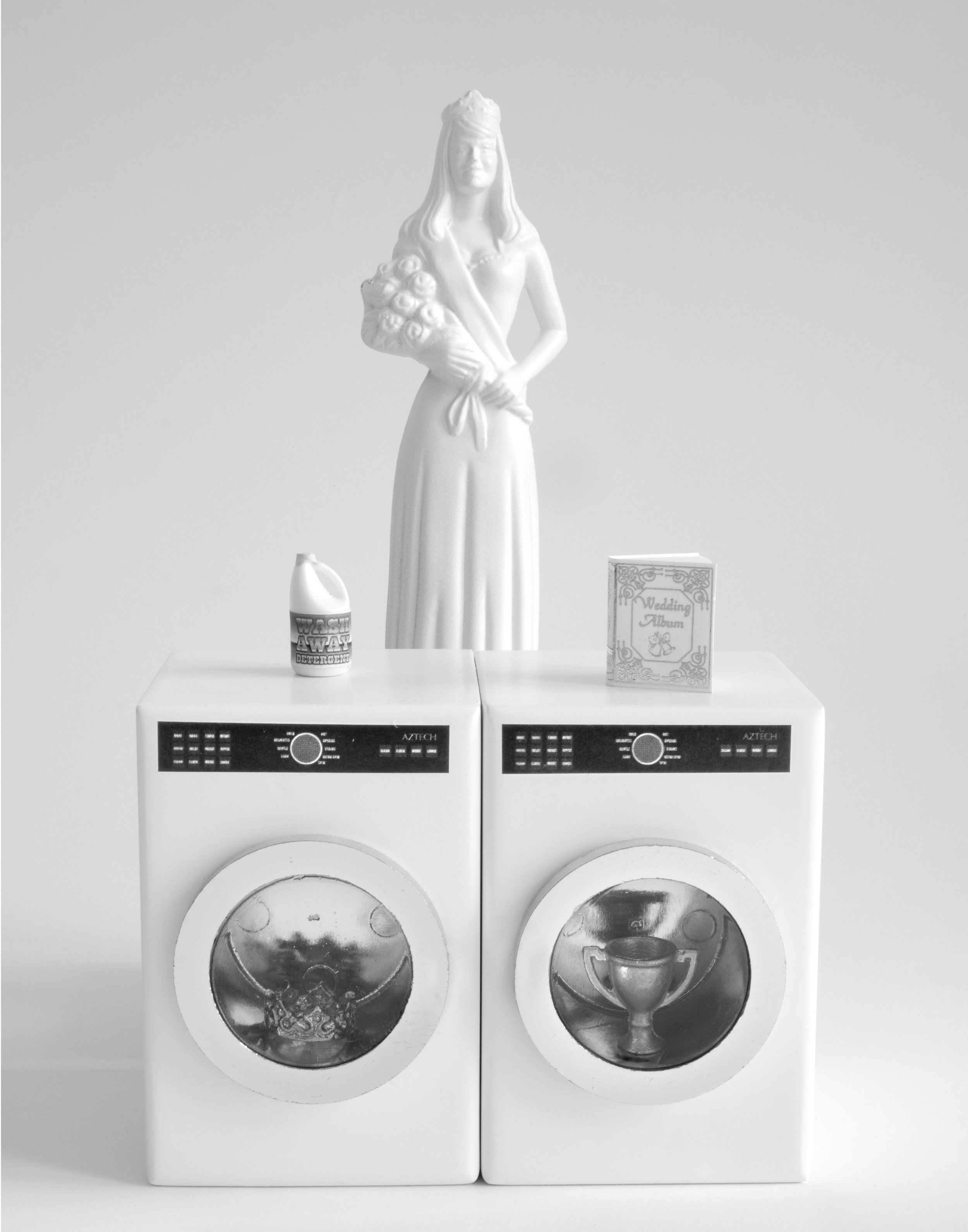 "White Dress and Matching Appliances , 2010  Photograph in archival ink on rag paper  26 x 32 inches  In  White Dress and Matching Appliances,  the beauty queen stands behind a matching washer and dryer set. Each machine contains a single item: in one, a crown; in the other, a trophy. A bottle of ""Wash Away"" detergent tops one machine. Like many of the works in the series, this piece comments on the dark underbelly of women's roles in domestic life. The work serves to humanize the figure of the beauty queen: her features may have been buffed away to anonymity, but her personal struggles are clear."