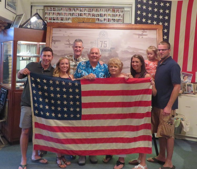 "Mary Freiberg and family returned to Hawaii with her uncle's ship flag that flew onboard the USS Rigel, ported in Pearl Harbor December 7th 1941. The flag was strafed by the attacking Japanese aircraft on the fantail of the ship and bears the scars of the attack with two bullet holes. Her uncle Cy was given the flag by an Admiral ""Husband"" as a gesture of gratitude for what the 18 year old signalman did that day. He and his crewmen took a small skiff from his ship during the attack and pulled burning sailors out of the harbor that were blown off the torpedoed ships tied up aside battleship row, saving numerous lives. Was the flag given to Cy by the Admiral Husband E. Kimmel??? We'll never know but his story and legacy live on in the Home of the Brave Museum!"