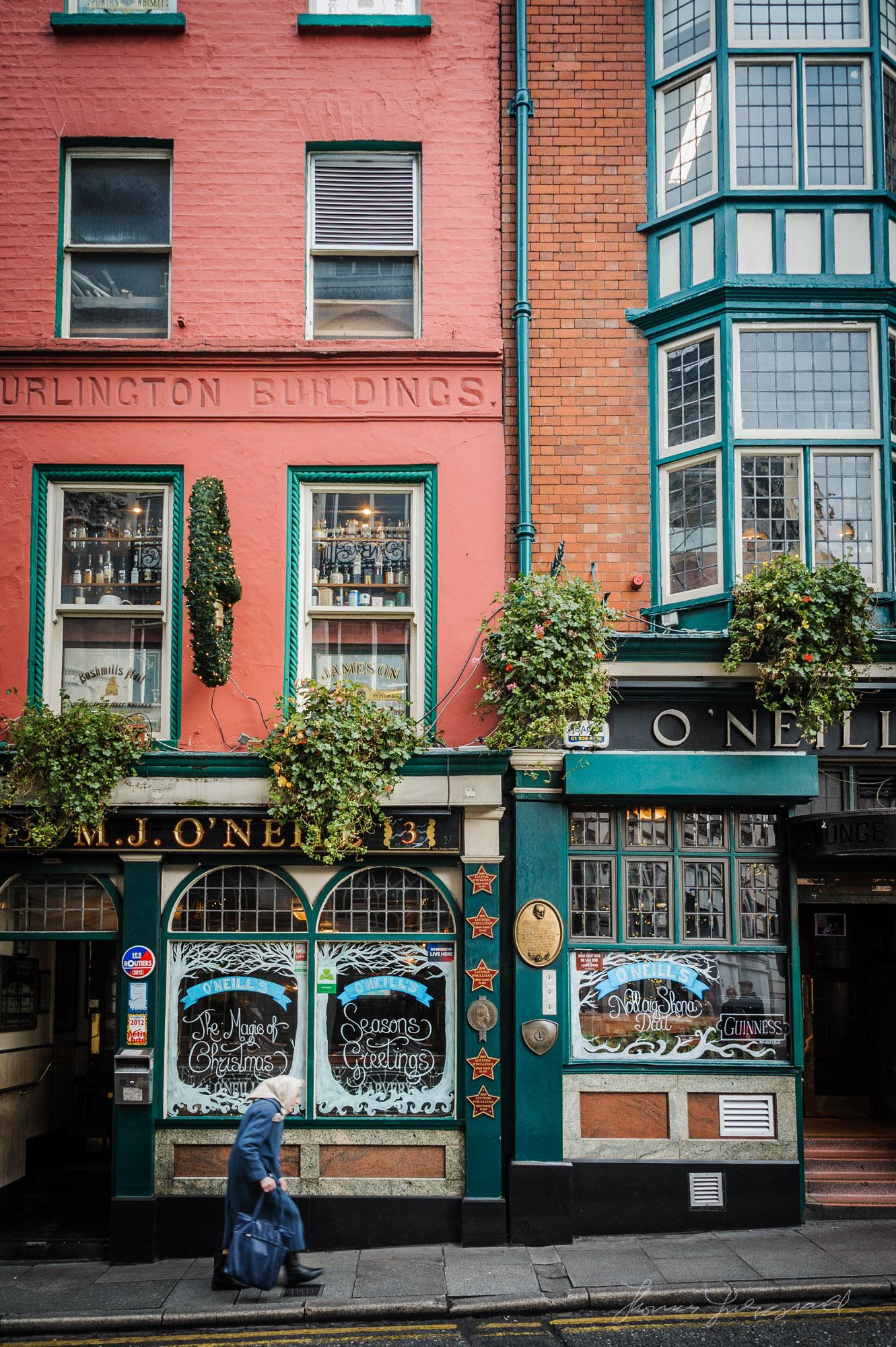 Old Lady walking by O'Neill's Pub in Dublin