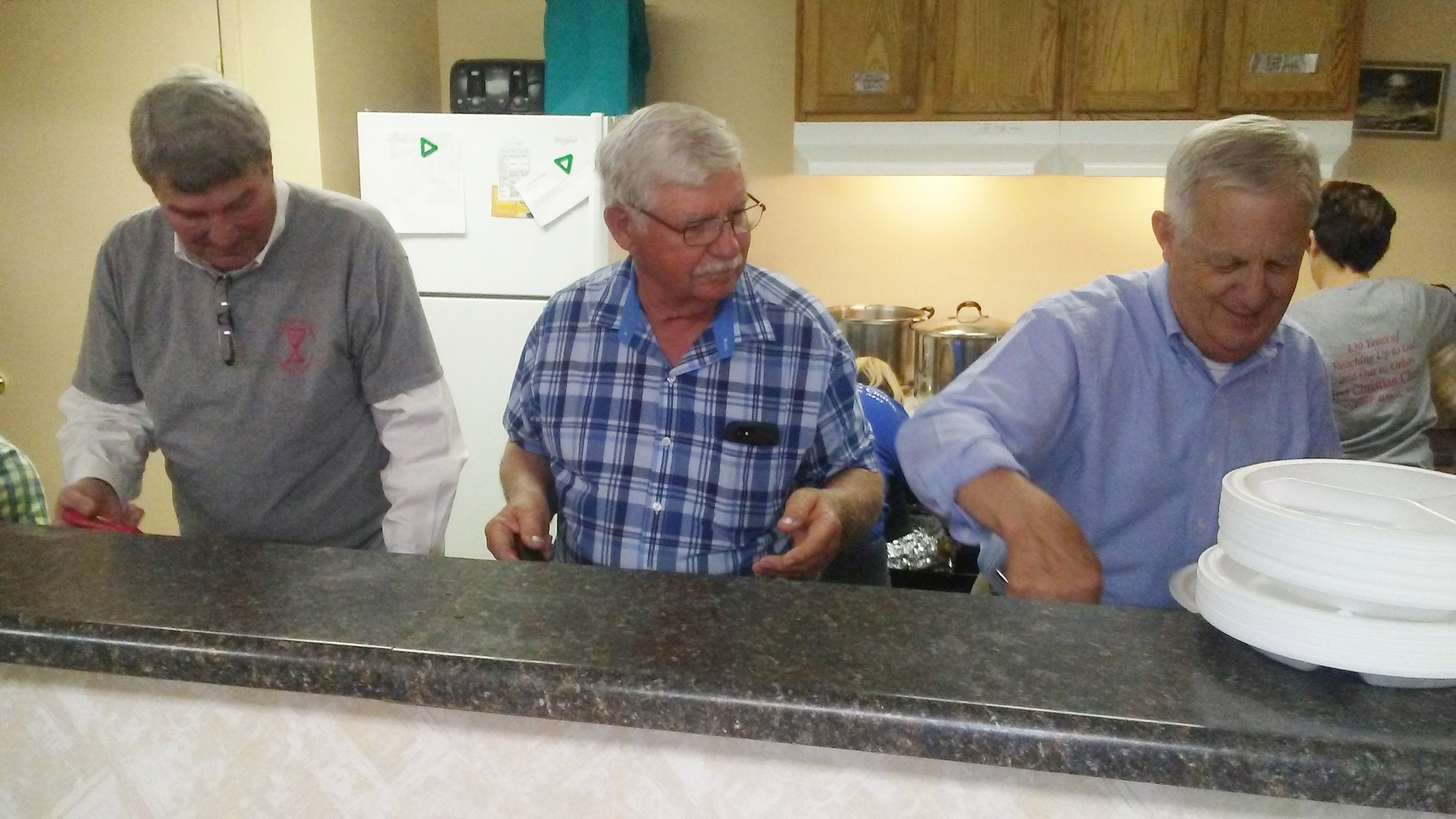 Mark Richardson, Stanley Pinkston, and Jack Maxwell serve up a meal for a Bread Shed guest.
