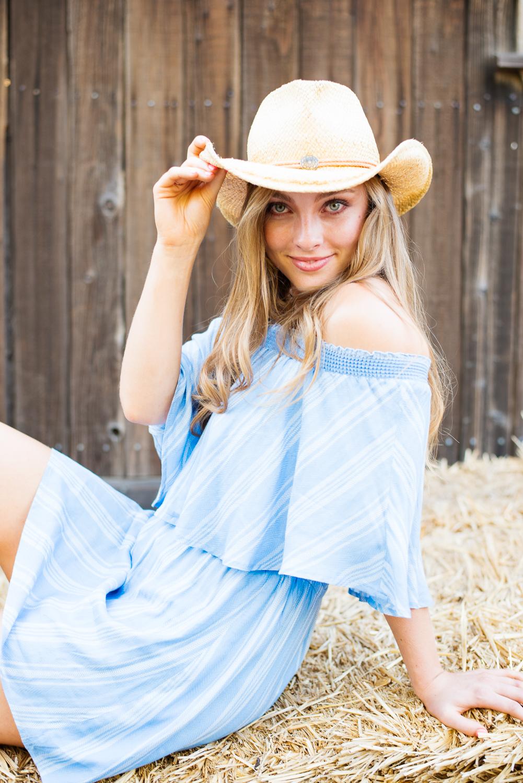 Outdoor high school senior photos in cowboy hat, sitting on some hay.
