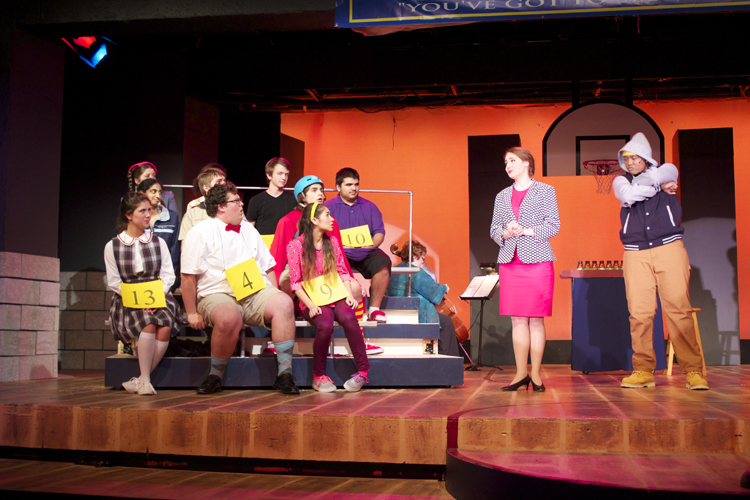 """When the contestants misspell a word, they are escorted offstage by """"comfort"""" counselor Mitch Mahoney, played by Kennedy Harris."""