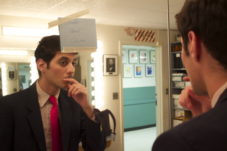 Arafat Quran checks out his mustache before taking the stage as vice principal Douglas Panch.