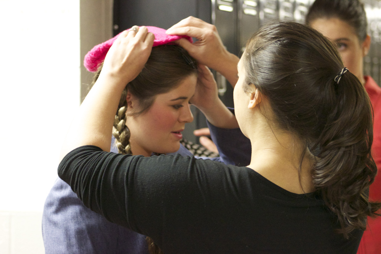Director Kirie Walz makes sure everything is just right on Kaylynn Coulter's costume before the dress rehearsal begins.