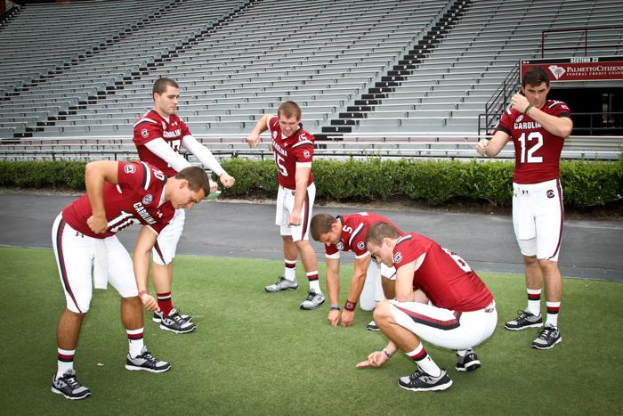 The team's quarterbacks do a little bit of lawn care at Williams-Brice.