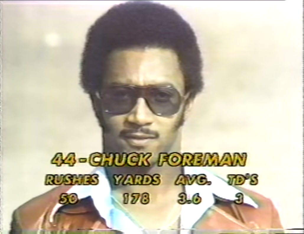 """Chuck Foreman looking good here, but also trying too hard to look good. The chains, the leather jacket, the shades, and the sideburns? Seems like a lot of """"cool guy"""" features for cool guy."""
