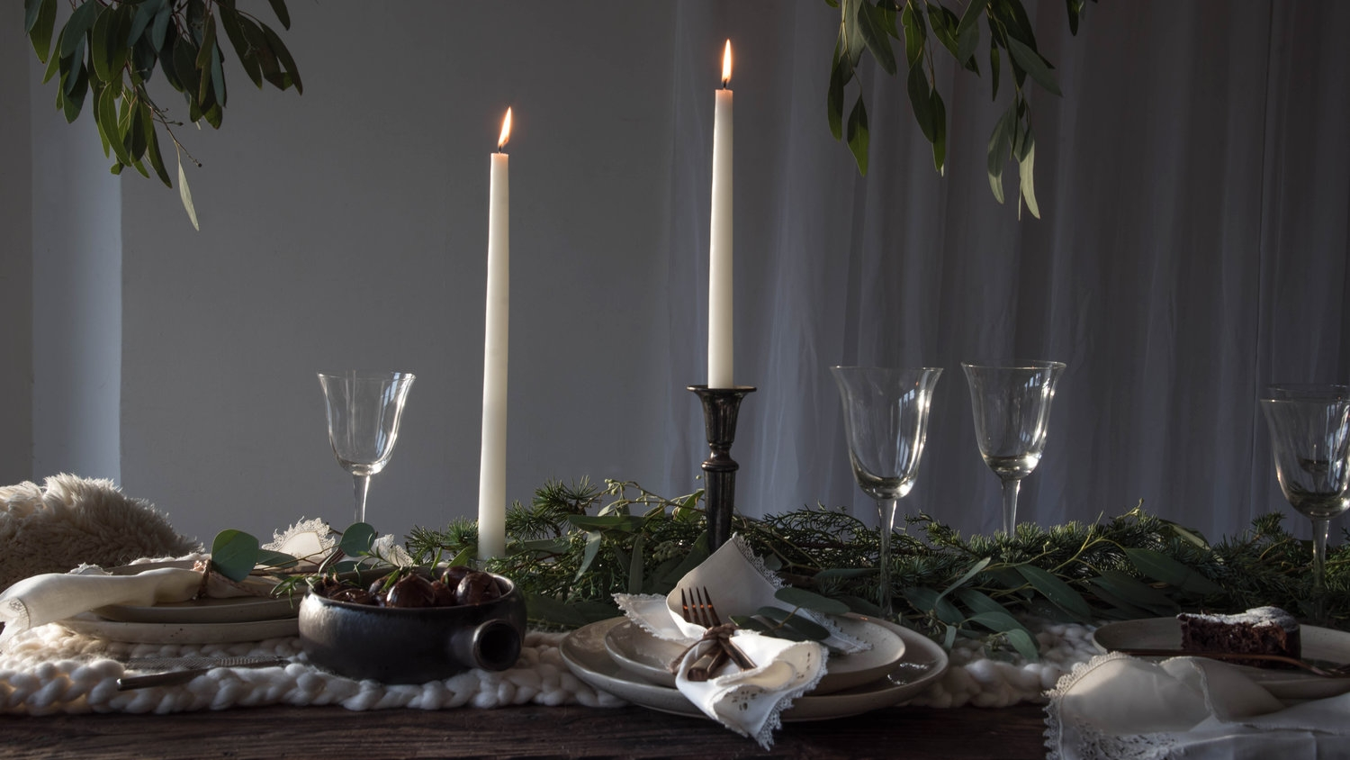 winter light - A holiday table setting inspired by a moody Nordic ambiance, where textures of wool and sheepskins combined with a bit of the outdoors in the form of various green branches.
