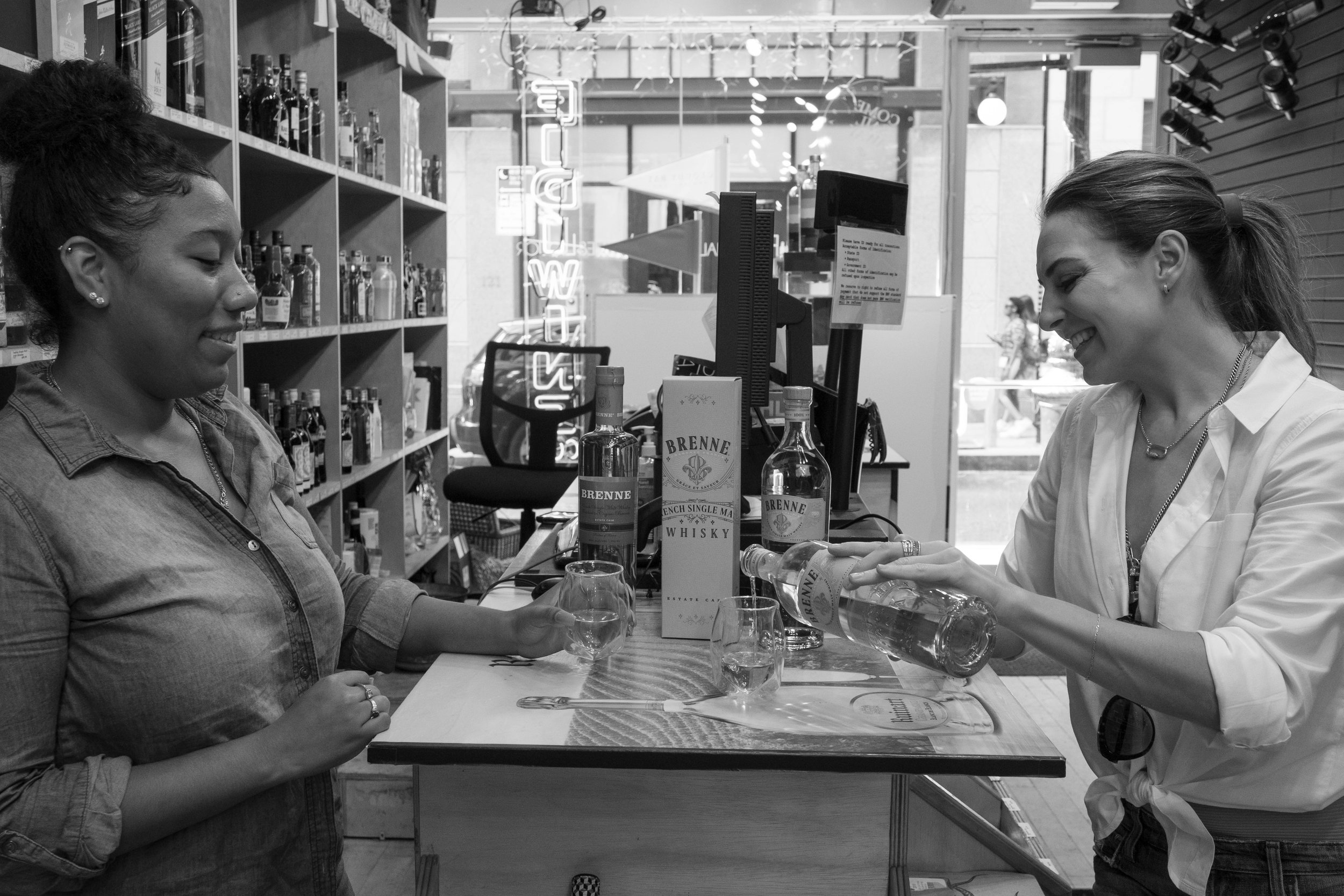 Part of Allison's business includes visiting liquor stores and doing tastings. Here, Allison is with Ashley Oseguera of  FiDi Wines  tasting a new batch of whisky.