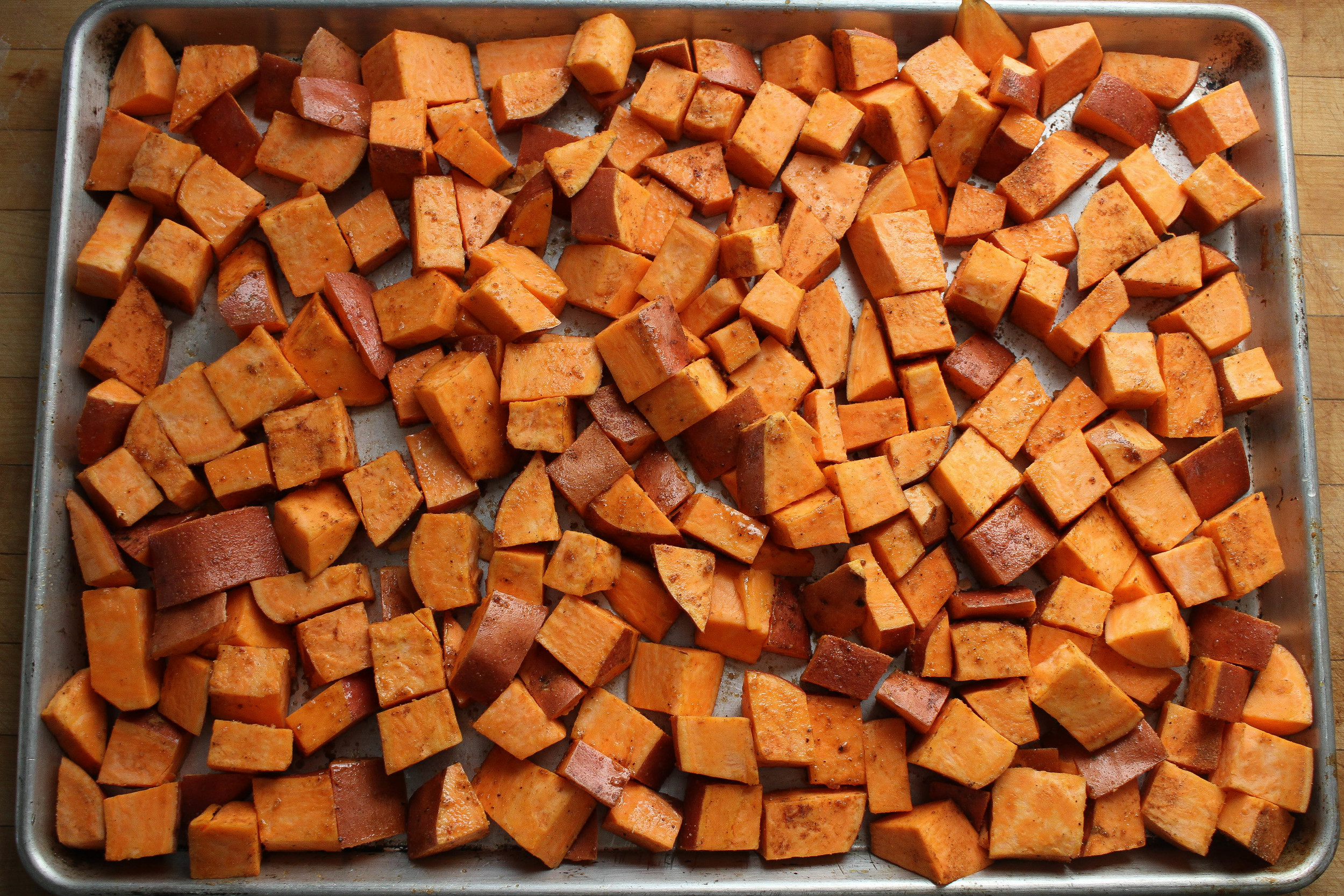 Sweet potatoes are coated and headed to the oven!