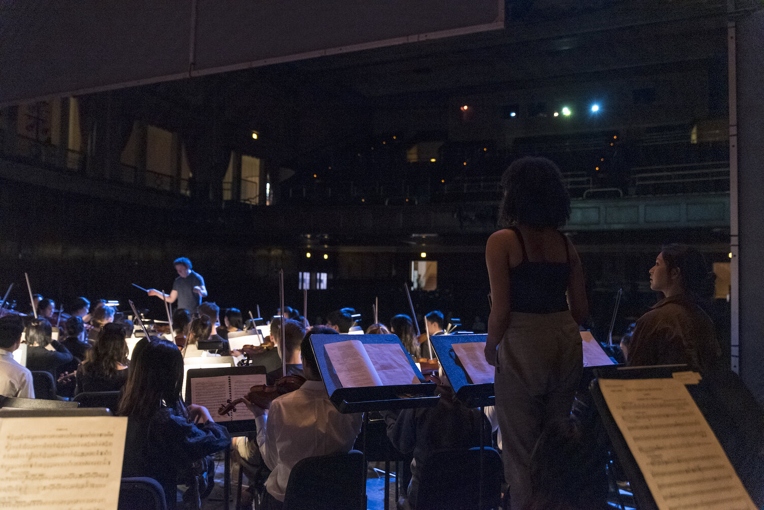 """Gustavo Dudamel rehearses Mendelssohn's """"A Midsummer Night's Dream"""" with the Princeton University Orchestra and Glee Club and student narrators from the Lewis Center for the Arts' Program in Theater (Victoria Davidjohn '19, Jacy Duan '21, and Kathryn McReynolds '20) before their final concert at the Patriots Theater at the War Memorial in Trenton, NJ, April 2019."""