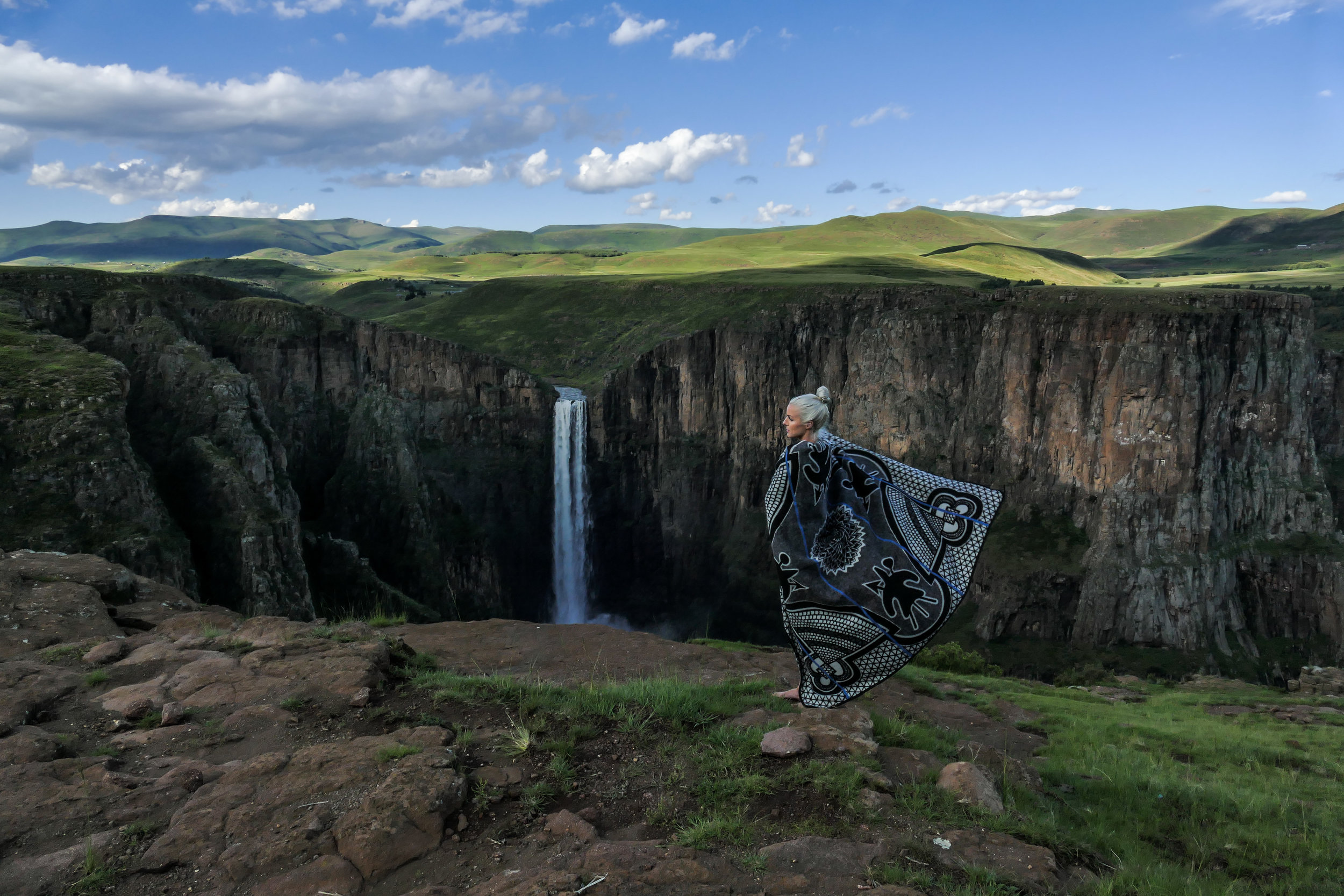 Adrienne McDermott at Maletsunyane Falls in Semonkong, Lesotho wearing a traditional Kharetsa (Spiral Aloe)pattern Basotho Blanket. Learn about purchasing a blanket at the end of this story. Image by Andrew McDermott @heyheyAndrew