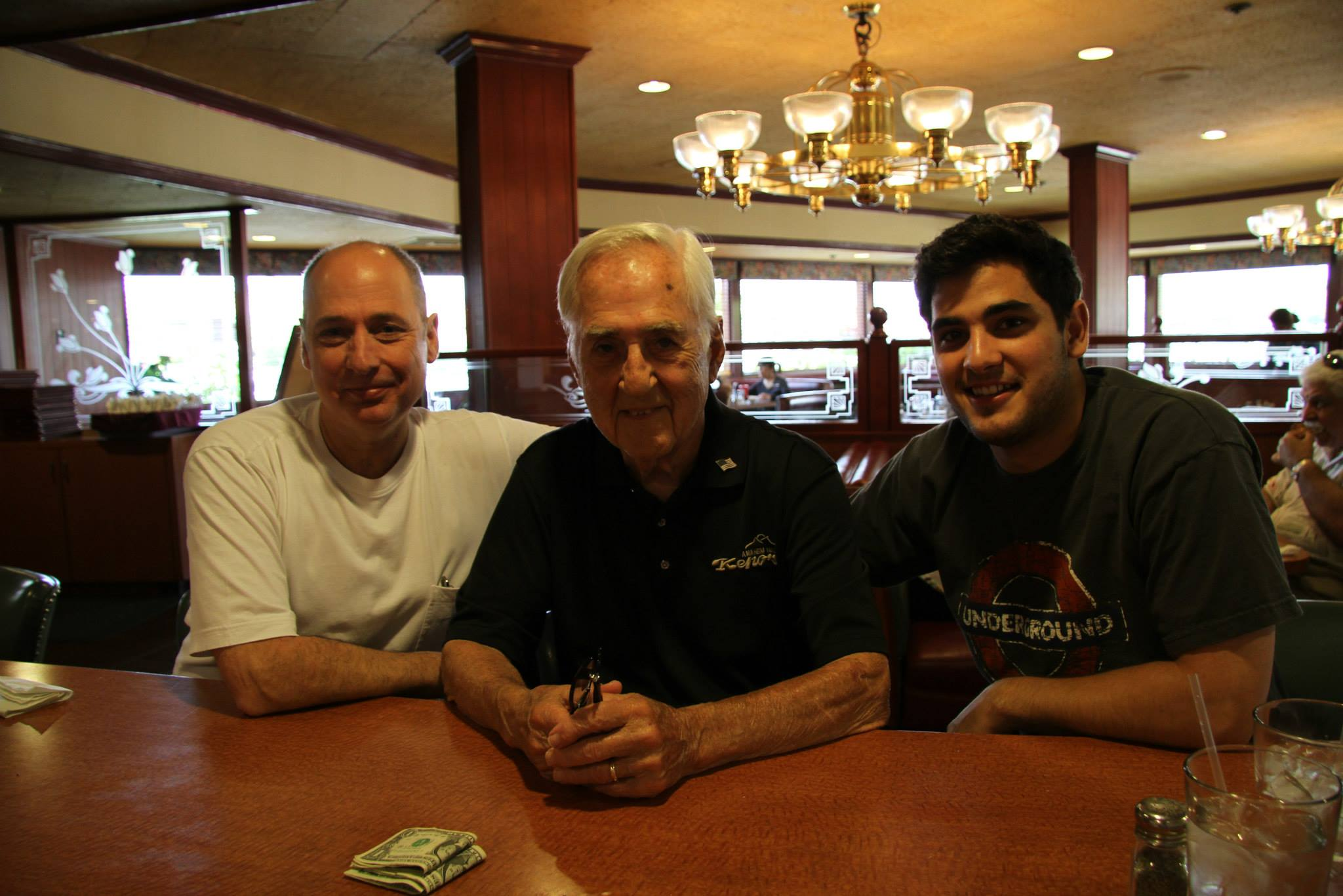 Three generations of Cooper men (Steve, Geno, Robert) pictured sitting on the Kenos counter.