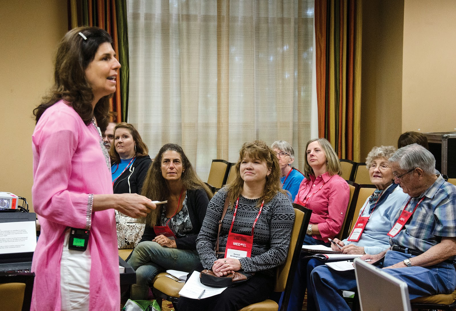 Nancy M. Williams speaking to a room of workshop participants on living with a hearing loss while pursuing her passion as an amateur pianist