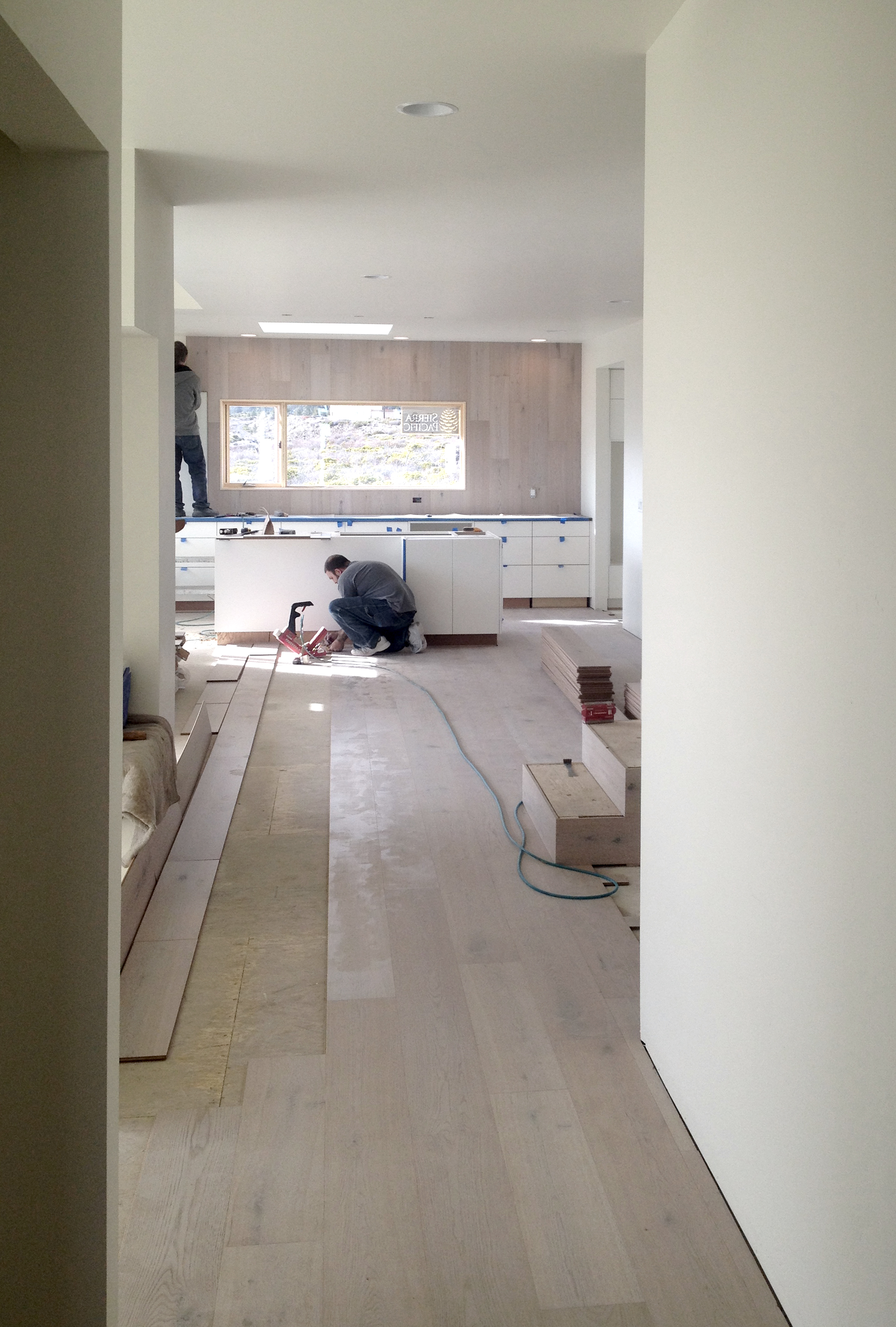 Lot 7 - Wood flooring being installed, wrapping up the wall beyond the kitchen cabinetry