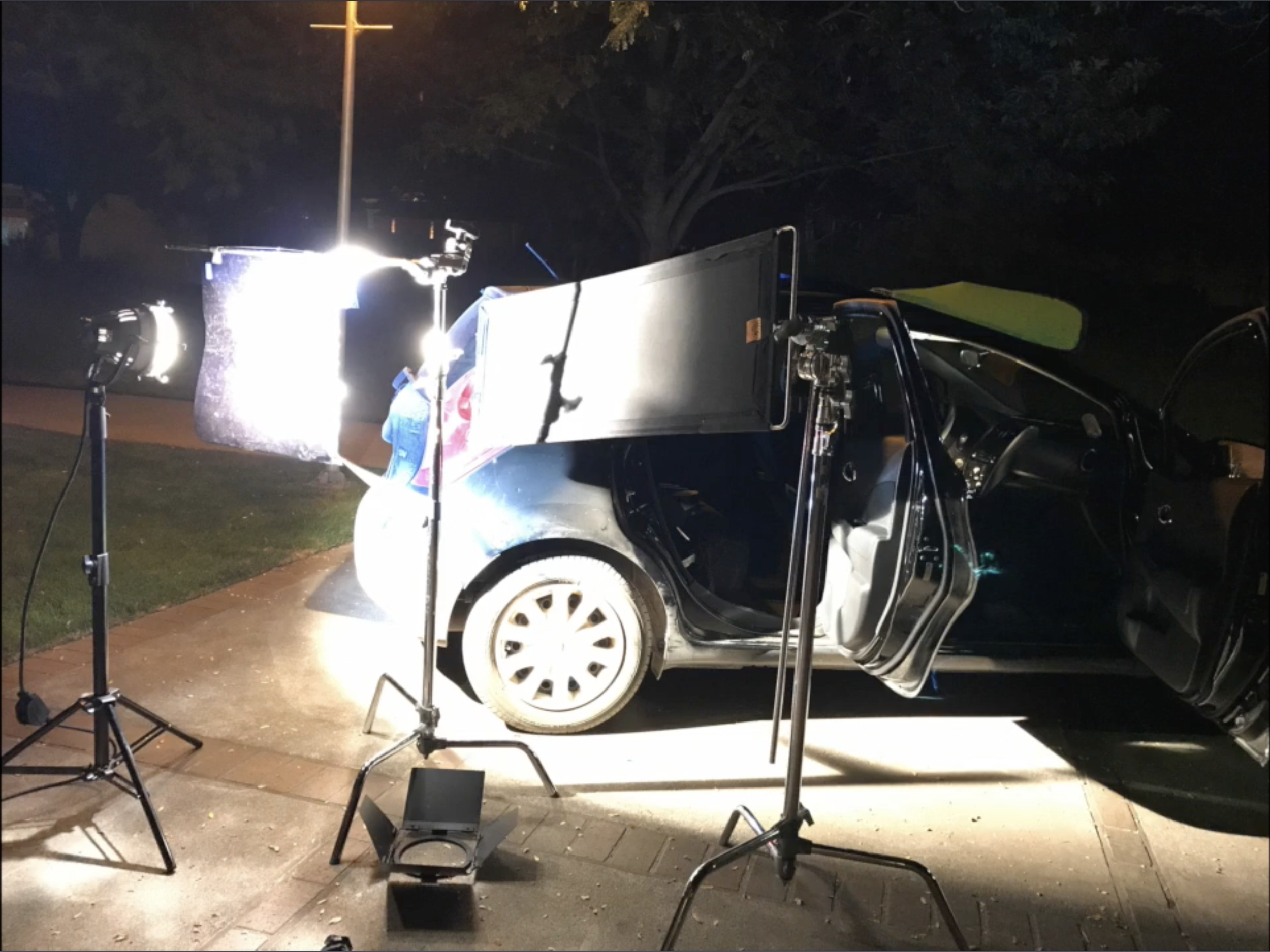 A student sets up lights for a scene inside a car.