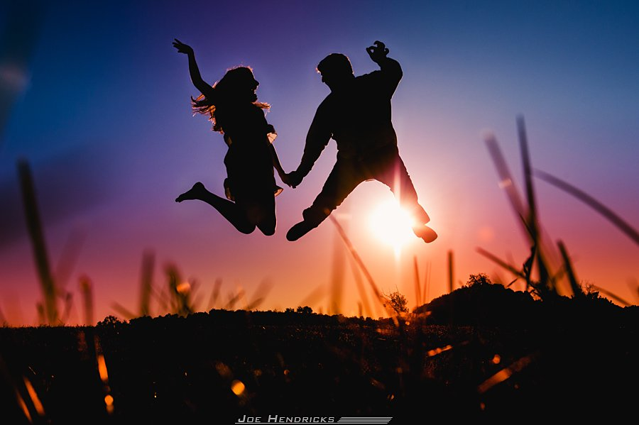 A fun couple jumping in the air at Sunset!