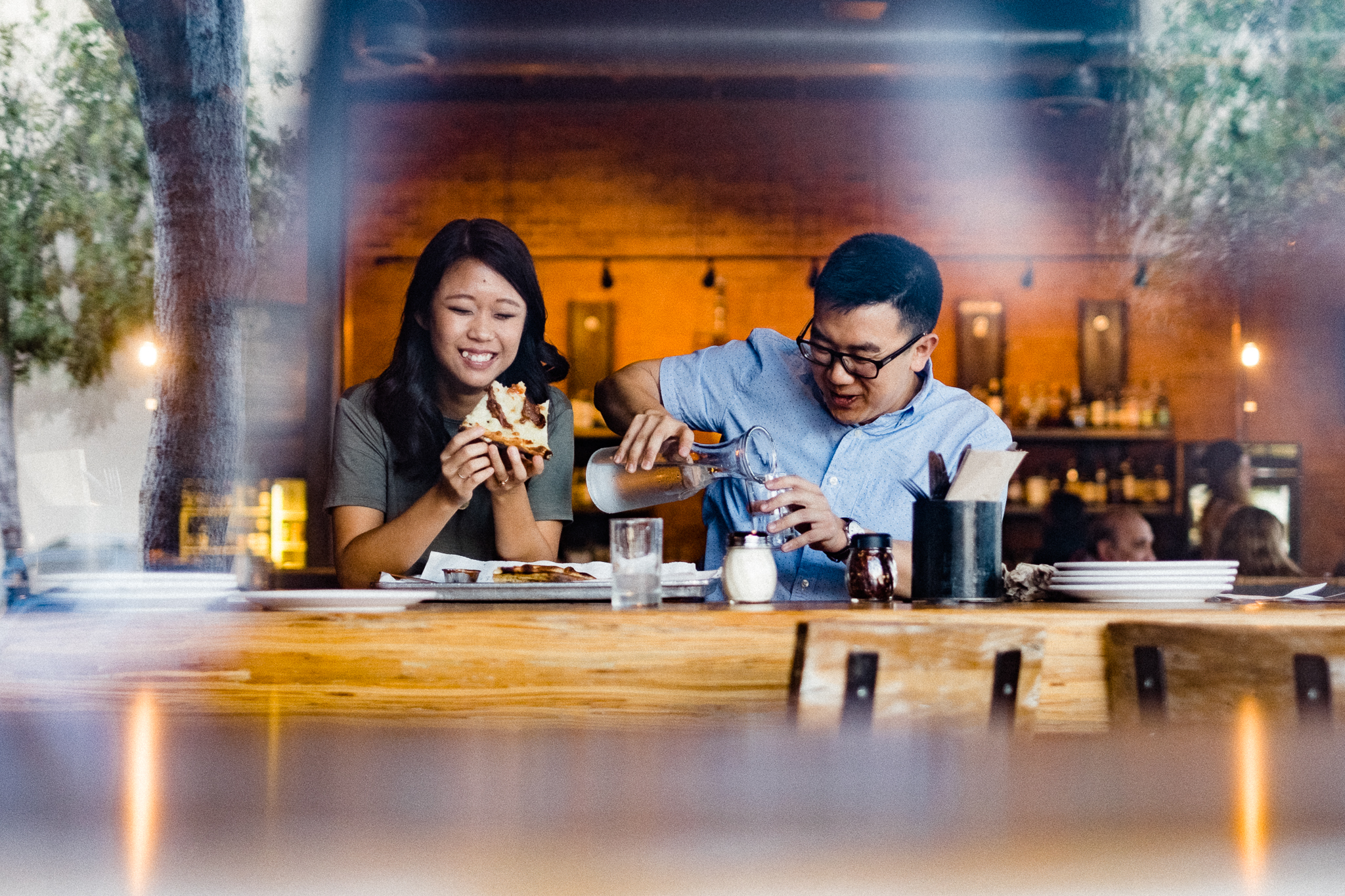 couple eating pizza during engagement session at URBN North Park