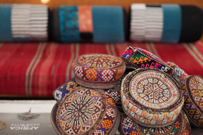 Antique embroidered caps from Afghanistan,  couch upholstered with a Moroccan blanket (Interior design at Peacock Pavilions - MyMarrakesh, M.Montague)