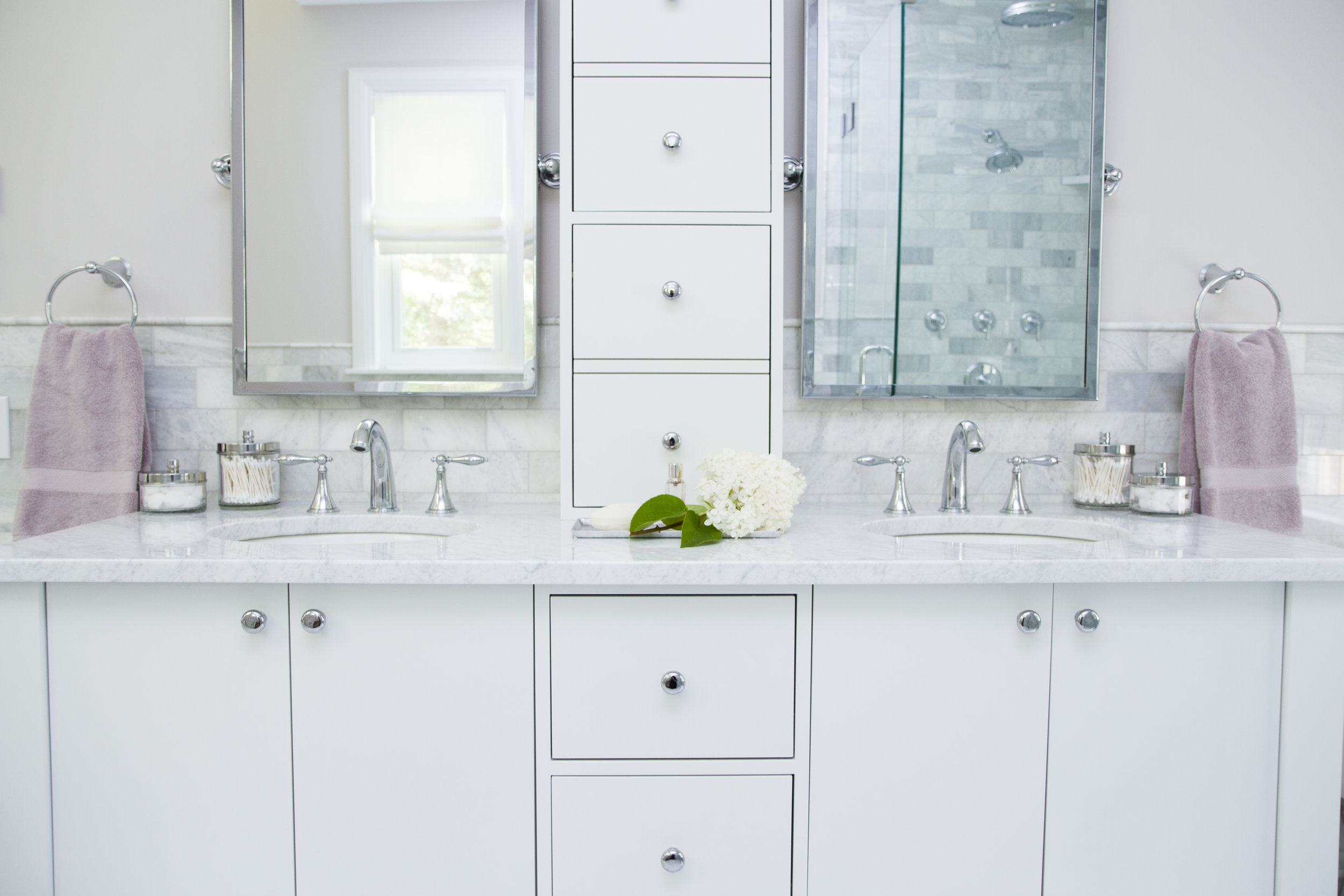 This bathroom vanity is similar to some of the others on the market, but there are a few distinct differences that we were able to include by going custom. The space for the vanity was a little larger than standard, so we made it fit the space better. Additionally, we hid some outlets inside those top cabinets, which means no ugly outlets or holes in the beautiful marble! One little trick? Those top cabinets were built to look like the drawers below, but they are actually cabinet doors that swing open. By making them look like drawers, we give the whole piece a very consistent and streamlined look.