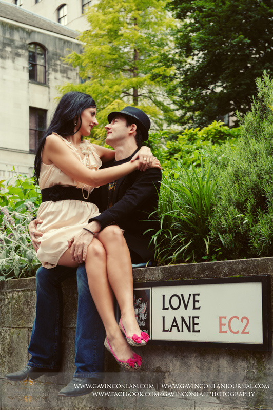 couple sitting on a wall cuddling at Love Lane EC2. London engagement photography by  gavin conlan photography Ltd