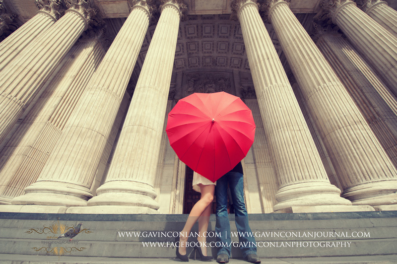 fun portrait of the couple hiding behind a red heart shaped umbrella on the steps of St Pauls Cathedral. London engagement photography by  gavin conlan photography Ltd