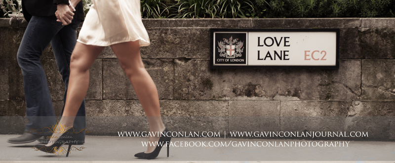 creative portrait of the couple walking past the Love Lane EC2 street sign. London engagement photography by  gavin conlan photography Ltd