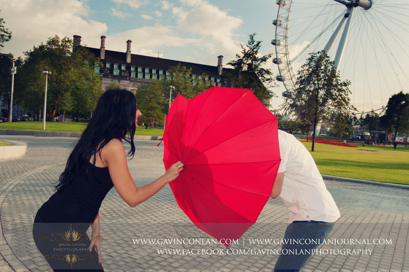 creative and fun couple portrait playing with the red heart shaped umbrella. London engagement photography by  gavin conlan photography Ltd