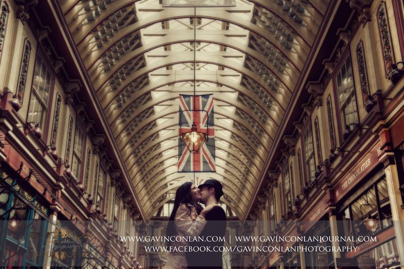 couple kissing under a Union Jack flag at Leadenhall Market. London engagement photography by gavin conlan photography Ltd