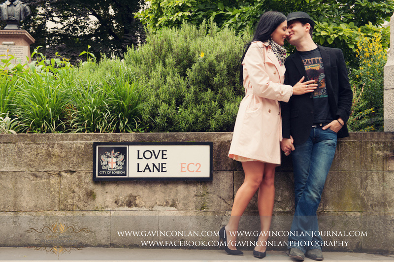 creative full length portrait of the couple standing on Love Lane EC2. London engagement photography by  gavin conlan photography Ltd