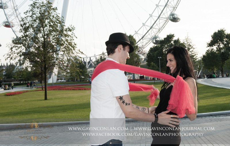 fun couple portrait as they play with a red scarf outside the London Eye. London engagement photography by  gavin conlan photography Ltd